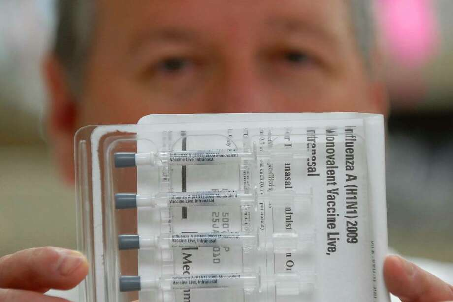 Michael Belemjian, director of the pharmacy at Albany Medical Center, displays five doses of the intranasal  H1N1 influenza vaccine Wednesday. (Paul Buckowski / Times Union) Photo: PAUL BUCKOWSKI