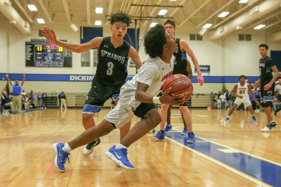 Dickinson Gators guard Ronny Nguyen (center) drives the ball to the basket during their game against the Clear Springs Chargers in Dickinson. Photo: Leslie Plaza Johnson, Freelancer / Freelance