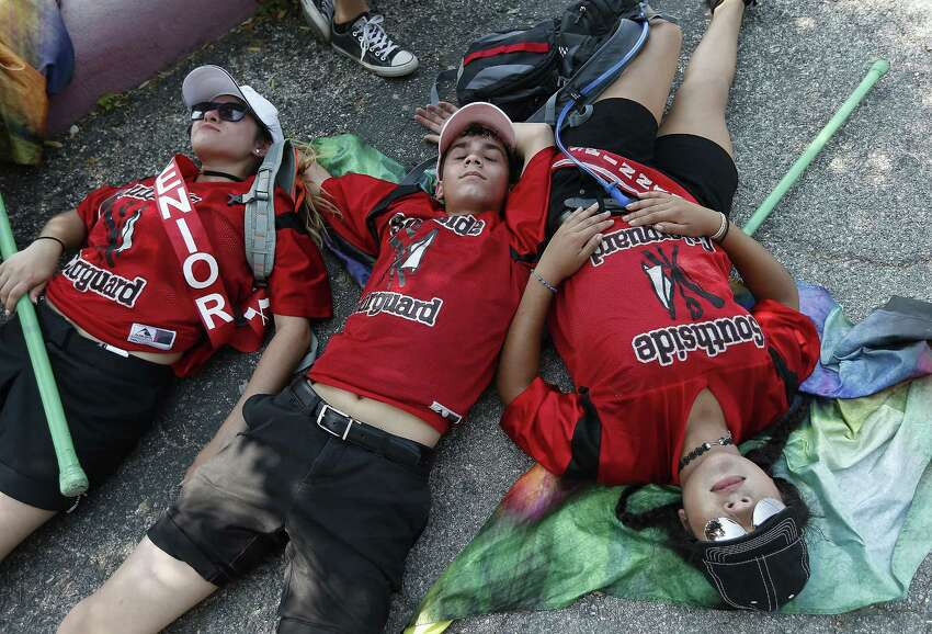 Battle of Flowers 2017: Southside High School flag members Clarissa Cantu (from left), Alejandro Ramirez and Nubia De La Garza lay on the ground after completing the route of the Battle of Flowers parade. With hot temperatures reaching into the mid-90s, the heat wore on participant and spectators throughout the parade.
