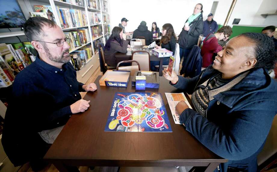 Keith Iodice, left, of Fairfield and Sandy Booth of Norwalk play Brain Games at Hawkwood Game Cafe in Milford. Photo: Arnold Gold / Hearst Connecticut Media / New Haven Register
