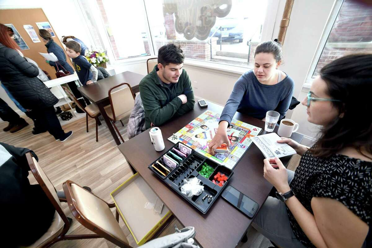 From left, Connor Pineiro and his sisters, Stephanie and Teresa, of Milford play Monopoly Bob's Burgers at Hawkwood Game Cafe in Milford.