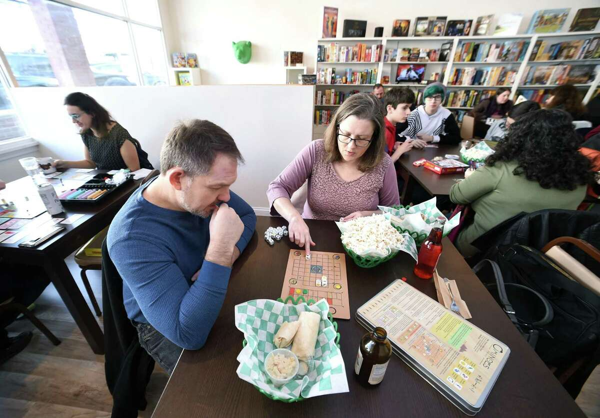 Jason Cook, left, and his wife, Jeri Ann, of Stratford play Ominoes at Hawkwood Game Cafe in Milford.