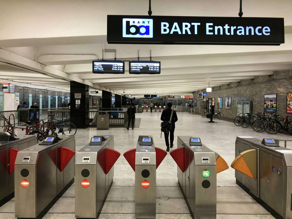 Digital screens showing delays and departure times at the Civic Center BART station.