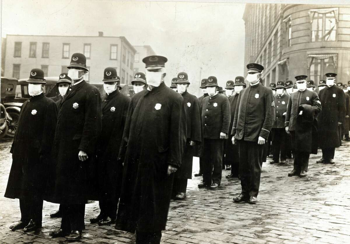 Police officers in Seattle are pictured in this December 1918 photo wearing masks made by the Seattle Chapter of the Red Cross during the influenza epidemic. Click through the gallery to see headlines from the Seattle Post-Intelligencer and photos from the 1918 Spanish flu pandemic.