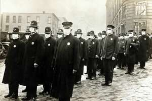 Police officers in Seattle are pictured in this December 1918 photo wearing masks made by the Seattle Chapter of the Red Cross during the influenza epidemic