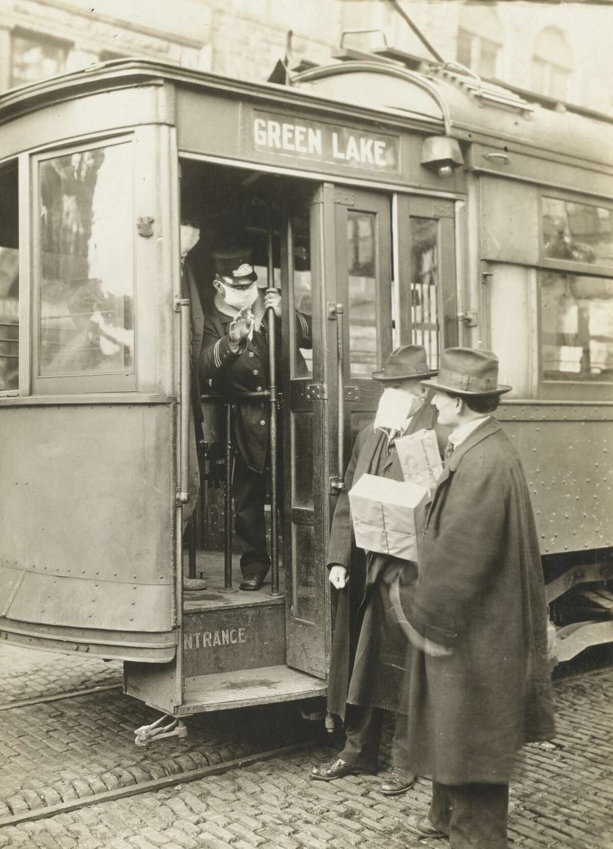 Flue precautions taken in Seattle during the Spanish Influenza epidemic meant no one to ride the street cars without wearing a mask. Photo dated December 1918.