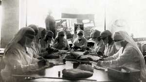 Nurses are pictured at work in Red Cross rooms in Seattle, with influenza masks. Pictured December 1918.