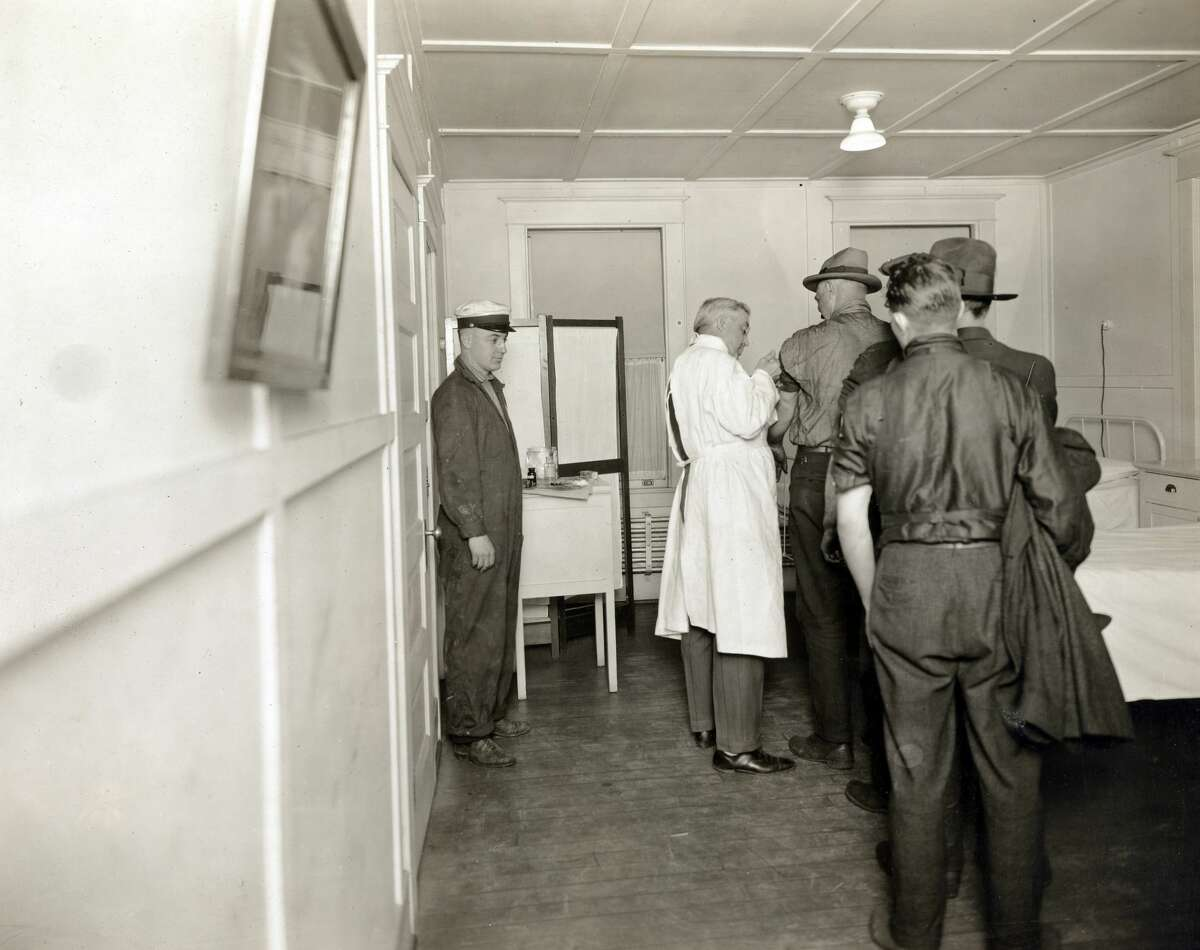Men are pictured in this December 1918 photo receiving flu vaccine injections in Seattle. The vaccine was wholly ineffective.