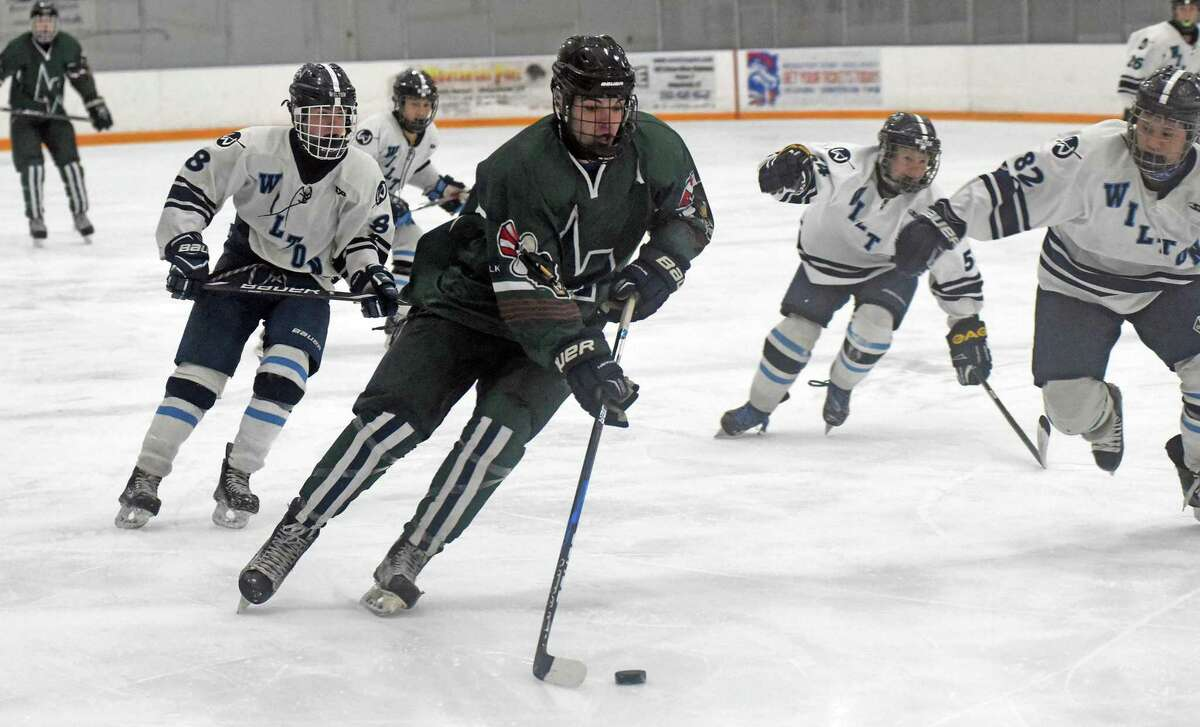 Norwalk-McMahon?'s Kevin Remson, center, skates with the puck while being chased, from left, by Wilton?'s Jackson Kelley, Nick Furst and Kevin Fung during Wednesday?'s FCIAC boys hockey game at the Winter Garden Arena in Ridgefield.