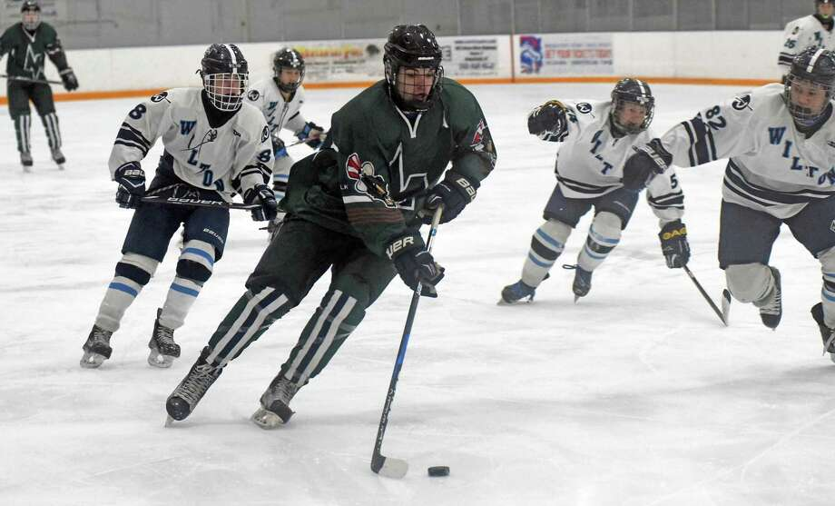 Norwalk-McMahon's Kevin Remson, center, skates with the puck while being chased, from left, by Wilton's Jackson Kelley, Nick Furst and Kevin Fung during Wednesday's FCIAC boys hockey game at the Winter Garden Arena in Ridgefield. Photo: John Nash/Hearst Media Connecticut