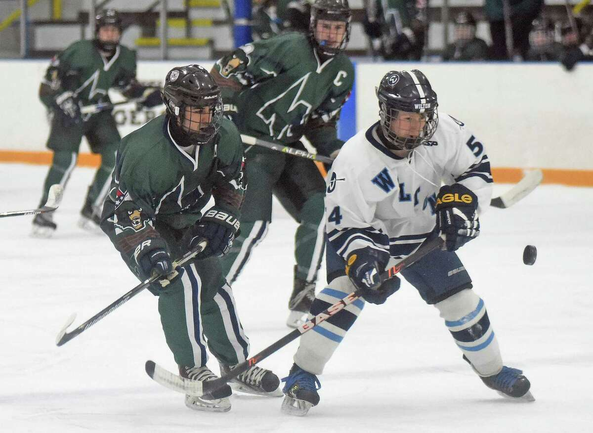 Wilton?'s Nick Furst, right, keeps his eye on the bouncing puck as Norwalk-McMahon?'s Stephen Pare, left, and Remy Gibson look on during Wednesday?'s FCIAC boys hockey game at the Winter Garden Ice Arena in Ridgefield.