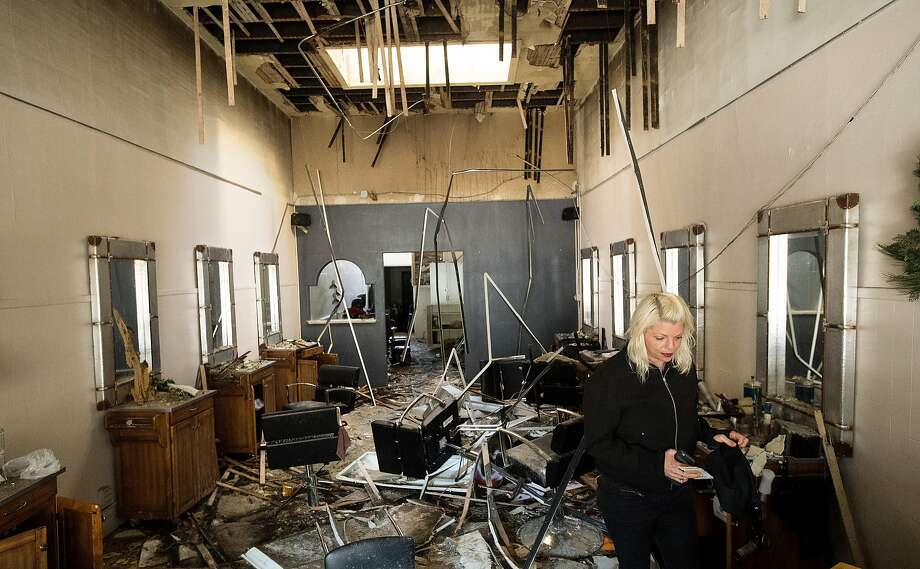 Elana Weinstein searches for her business license among the remains of the Sloane Square Beauty Salon that was damaged during a fire. Photo: Noah Berger, Special To The Chronicle