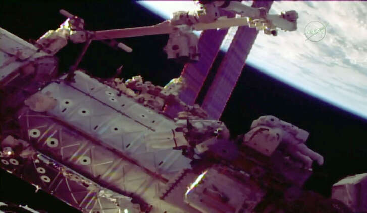 This NASA TV video grab image shows NASA astronauts Mark Vande Hei, left, and Scott Tingle as they step out on a spacewalk to repair the robotic arm at the International Space Station. ( AFP PHOTO / NASA TV / Handout)