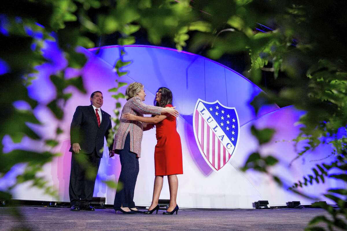 In this July 14, 2016, photo, Democratic presidential candidate Hillary Clinton, accompanied by LULAC President Roger Rocha (left), hugs University of Texas student Dreamer Lizeth Urdiales as she arrives to speaks at the 87th League of United Latin American Citizens National Convention in Washington. Rocha is facing harsh criticism for endorsing President Donald Trump's immigration framework that includes a border wall.