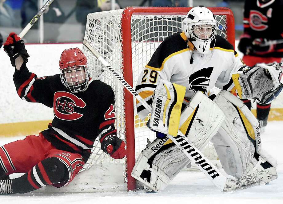 Cheshire sophomore forward Matthew Vendetto gets knocked into the net as Amity senior goalie Michael Holloway keeps his eye on the puck, Wednesday, Jan. 31, 2018, at Bennett Rink in West Haven. The game ended in a 4-4 tie in regulation and a scoreless overtime. Photo: Catherine Avalone, Hearst Connecticut Media / New Haven Register