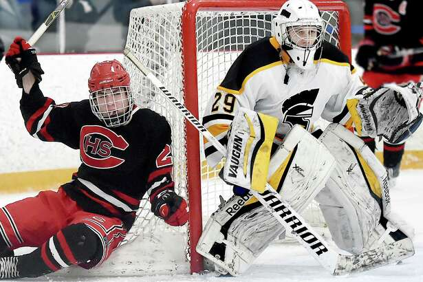 Cheshire sophomore forward Matthew Vendetto gets knocked into the net as Amity senior goalie Michael Holloway keeps his eye on the puck, Wednesday, Jan. 31, 2018, at Bennett Rink in West Haven. The game ended in a 4-4 tie in regulation and a scoreless overtime.