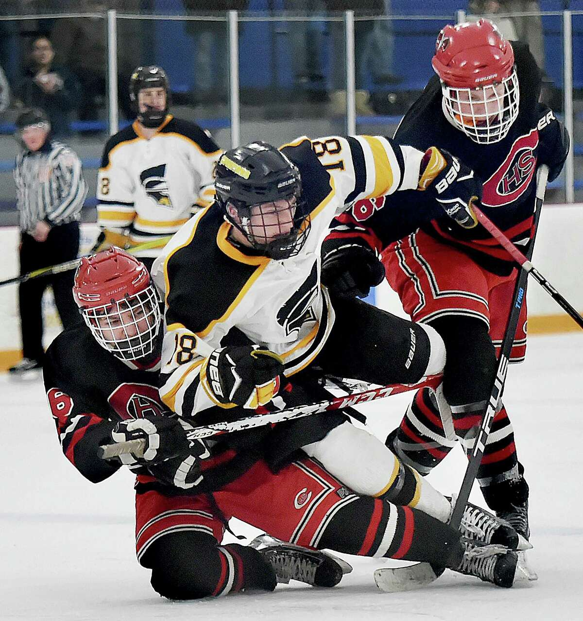 Amity junior forwared Jason Csejka (18) battles Cheshire junior forwards Jason McKinley (6) and Evan Veivia (16), Wednesday, Jan. 31, 2018, at Bennett Rink in West Haven. The Spartans tied the Rams, 4-4 in regulation, and a scoreless overtime.