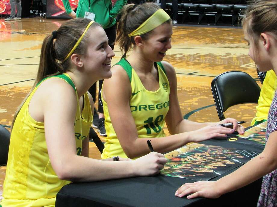 In this Sunday, Jan. 14, 2017 photo, Oregon's Sabrina Ionescu, left, signs autographs with teammate Lexi Bando following an NCAA college basketball game at Matthew Knight Arena in Eugene, Ore. Ionescu has gained attention with her triple-double record. But she's much more than a stat to the No. 7 Ducks, who are off to a 6-0 start in Pac-12 conference play. (AP Photo/Anne M. Peterson) Photo: Anne M. Peterson, Associated Press