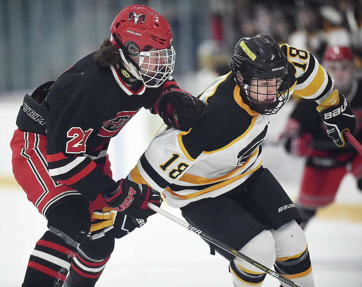 Amity's Jason Csejka and Cheshire's James Ilnicki battle for the puck on Wednesday.