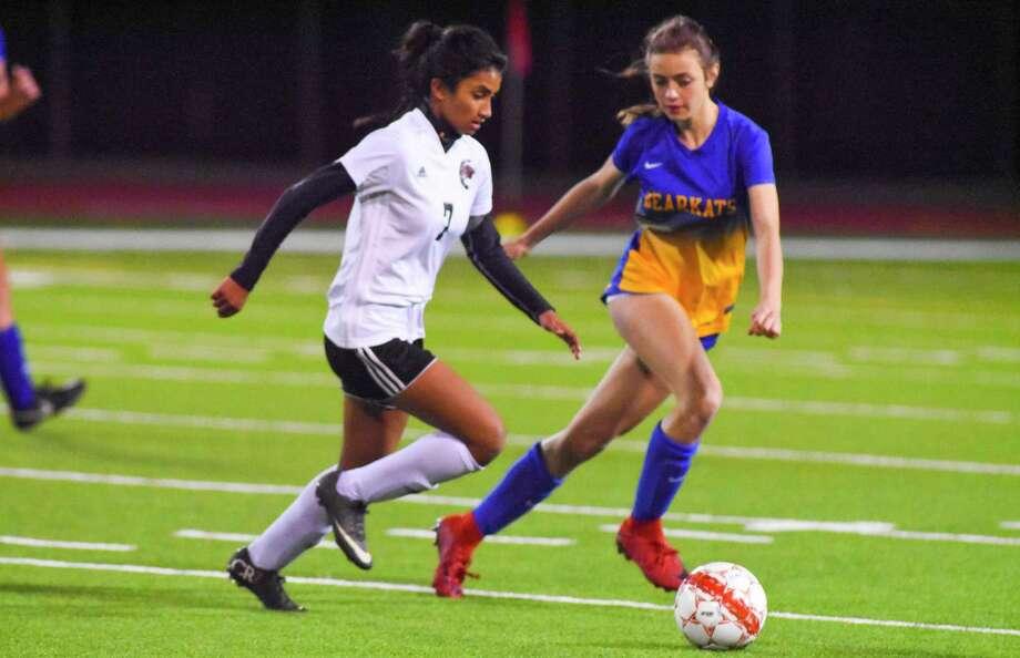 Langham Creek's Cami  Gutierrez tries to kick the ball past Cat Davis. Photo: Tony Gaines, Photographer