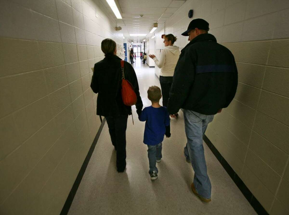 Cynthia Cabrera, Tom Fonck, and their son Tyler Fonck, 4, take a tour of the school building with PTO volunteer/ JFK parent Jane Geyfman during kindergarten registration at John F. Kennedy School in Milford on Wednesday, March 9, 2011.