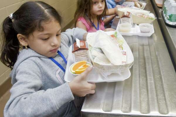 Kindergartner Cassandra Pardo carries her lunch to a table in the cafeteria at F.A. Berry Elementary School in Bethel Wednesday, Sept. 5, 2012. Included with her lunch are slices of oranges.
