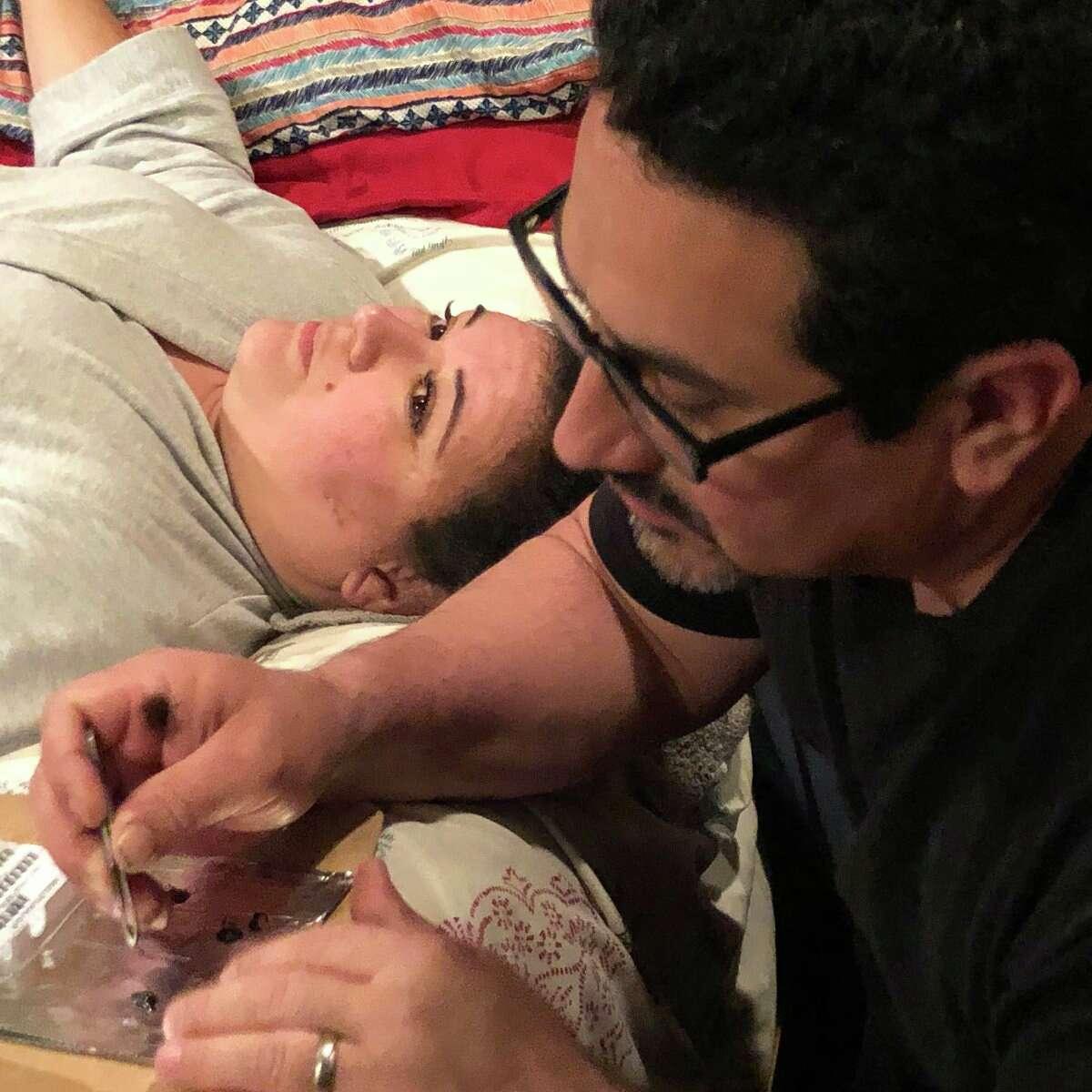Juan Vela applying eyelashes for his wife, Maricela Vela.
