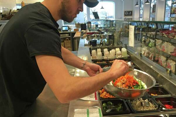 Chef Fausto Mieres combines ingredients for the Curry Up saute bowl at MIX Creative Kitchen in Greenwich.
