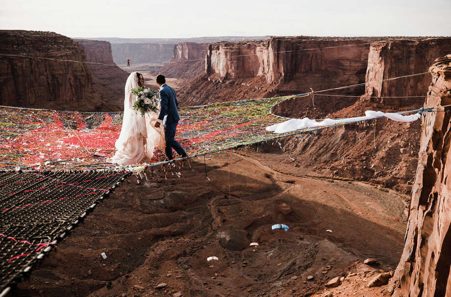 "Ryan Jenks and Kim Weglin, professional highliners who live in Lodi, Calif., got married on a ""spacenet"" 400 feet above a Utah canyon. (Photo by Hearnes Photography) Photo: (Courtesy Of Ryan Jenks And Kim Weglin / Photo By Hearnes Photography"
