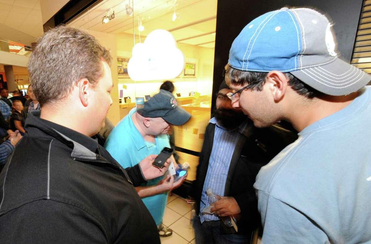 Oliver Bashan, right, one of the first in line for the new iPhone 4S gets a demonstration before his purchase by Nicholas Rust, left, business manager at the Apple store in Crossgates Mall in Albany, N.Y. October 14, 2011. The iPhone 4S was the first iPhone to have Siri preloaded on it. (Skip Dickstein/Times Union)