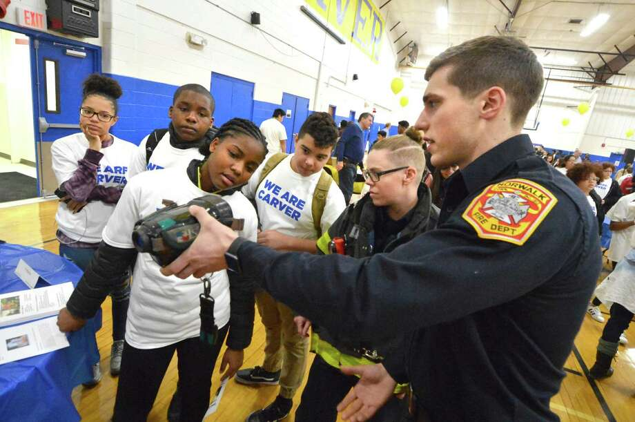 Norwalk Firefighters Christian Drenckhahn and Cat Macari demonstrate some of the department's firefighting tools like a Thermal Imaging camera to students, including Winderlie Toussaint during the Carver Center Annual Career Fair on Tuesday January 30, 2018 in Norwalk Conn. Photo: Alex Von Kleydorff / Hearst Connecticut Media / Norwalk Hour