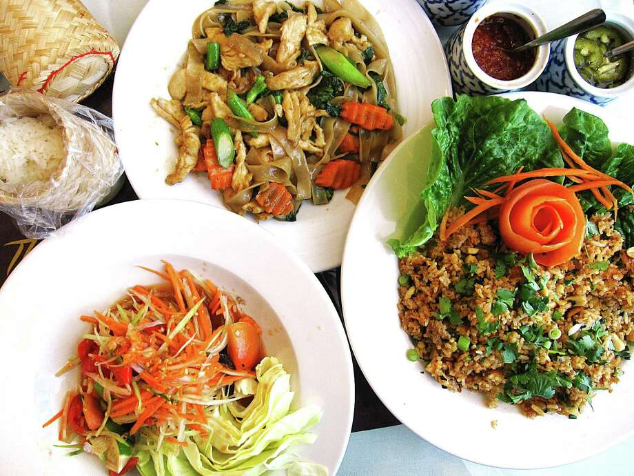 Papaya salad, bottom left, pad see ew with chicken and nam khao crispy rice salad from Thai Esan & Noodle House. Photo: Mike Sutter /San Antonio Express-News