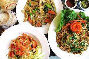 Papaya salad, bottom left, pad see ew with chicken and nam khao crispy rice salad from Thai Esan & Noodle House.