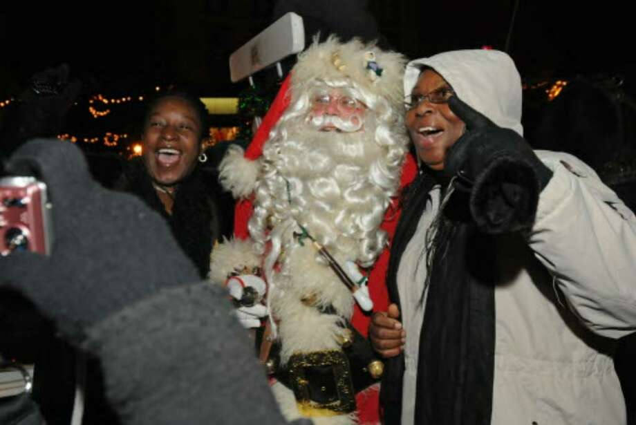 Michelle Spence, left, and Sylvia Williams, both of Saratoga Springs, get their photo taken with Santa by a friend Wednesday night before a tree lighting on Broadway in Saratoga Springs. (Lori Van Buren / Times Union)