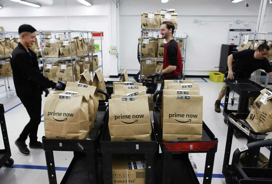 Associates load carts full in December 2017 at an Amazon Prime Now center where one-hour deliveries are filled, in San Francisco. Photo: Michael Macor / The Chronicle / ONLINE_YES