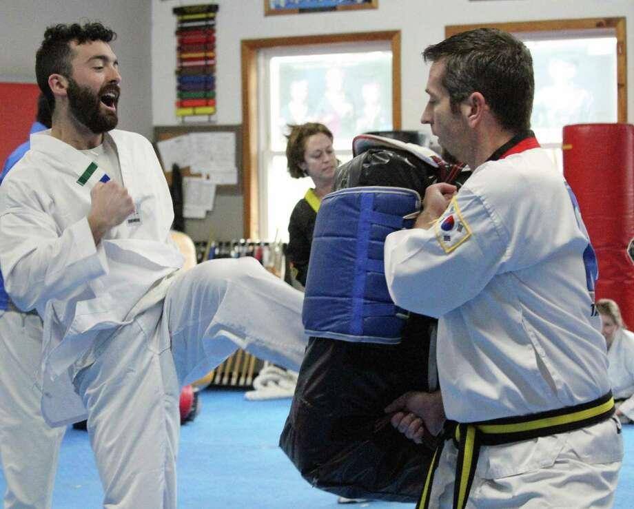 Hearst Connecticut Media reporter Justin Papp executes a side kick at World Champion Taekwondo in Fairfield on Jan. 29. Photo: Genevieve Reilly / Hearst Connecticut Media / Fairfield Citizen