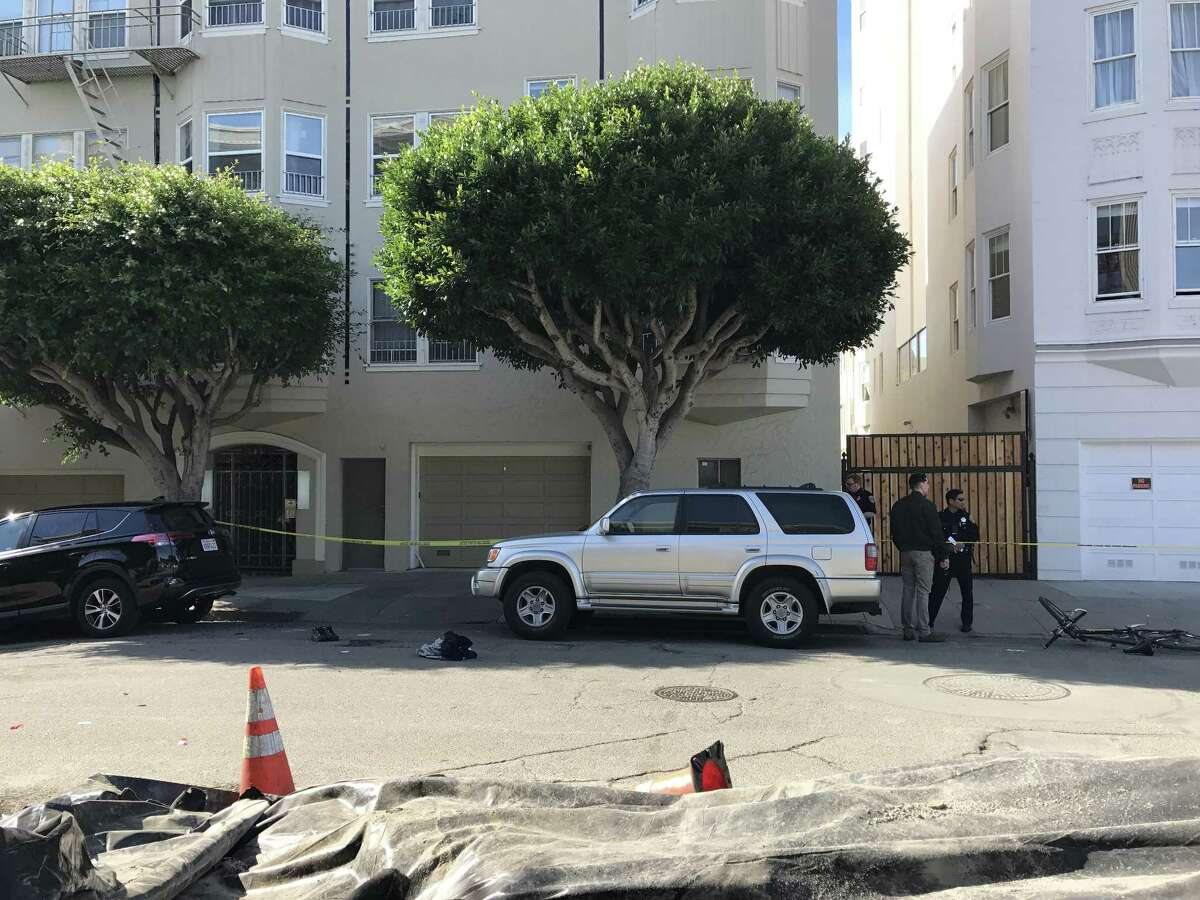 Officers stand at the scene at Hayes and Pierce streets in San Francisco where police said a fleeing auto burglary suspect struck a police officer.