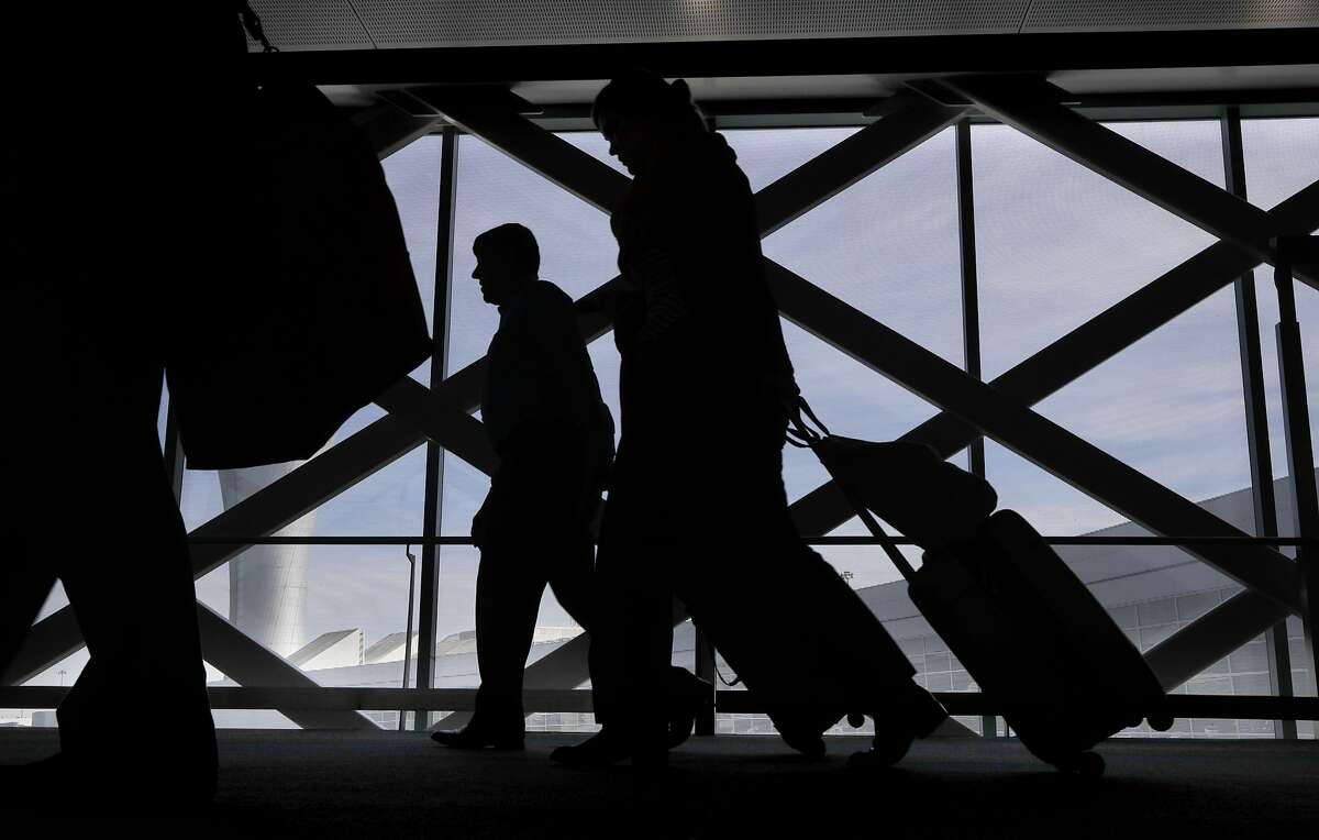 Travelers make their way to ground transportation at San Francisco International Airport on Thursday Feb. 1, 2018, in San Francisco, Calif.