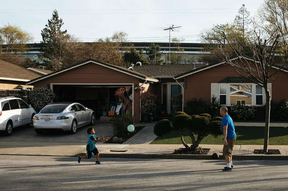 Edric Yamamoto and his son, Greyson Yamamoto, 7 play bounce outside their home in the Birdland neighborhood in Sunnyvale, Calif. Wednesday, Jan. 31, 2018. Yamamoto said that he doesn't mind the new Apple campus, which looms over his home. Photo: Mason Trinca, Special To The Chronicle