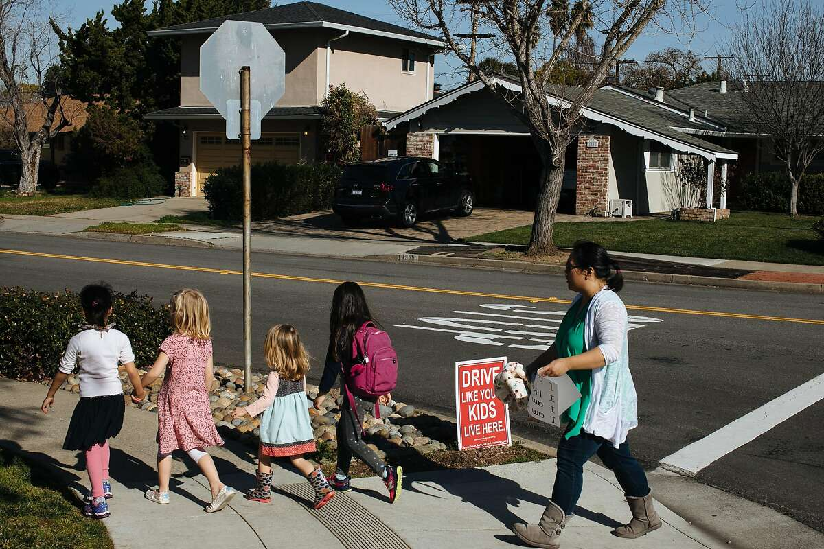 """Children walk past a sign that reads """"Drive Like Your Kids Live Here"""" in the Birdland neighborhood in Sunnyvale, Calif. Wednesday, Jan. 31, 2018. With 12,000 workers expected to move into Apple Park, residents have been seeing commuters traffic cut through their neighborhood to avoid the long traffic lights."""