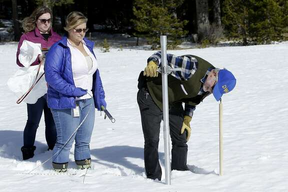 Frank Gehrke, right, chief of the California Cooperative Snow Surveys Program, for the Department of Water Resources, checks the snowpack depth as Courtney Obergfell, left, and Michelle Mead, center, both of the National Weather Service, look on during the second snow survey of the season Thursday, Feb. 1, 2018, near Echo Summit, Calif. The snow survey showed the snow pack at this location at 13.6 inches of deep with a water content of 2.6 inches. (AP Photo/Rich Pedroncelli)