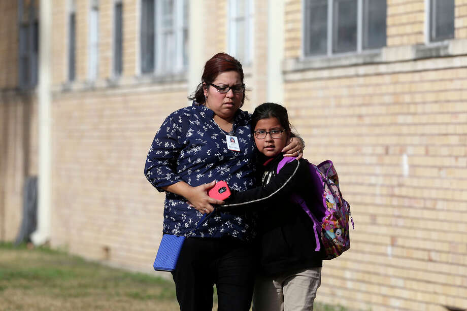 A woman leaves with a child at the Frank L. Madla Accelerated Collegiate Academy across the street of scene of a double shooting that took place Thursday February 1, 2018 on the 4100 block of South Presa. As of Thursday afternoon there was one fatality. Another victim suffered multiple gunshot wounds. Police are investigating the circumstances of the shooting. Photo: John Davenport, San Antonio Express-News / ©John Davenport/San Antonio Express-News