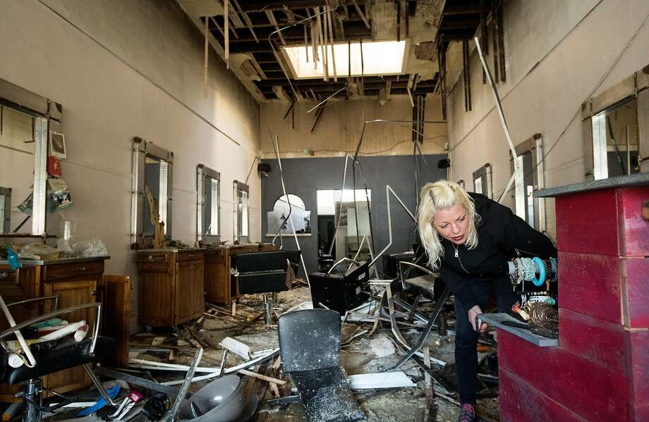 Elana Weinstein searches for the business license for her Sloane Square Beauty Salon damaged in the blaze. Photo: Noah Berger, Special To The Chronicle