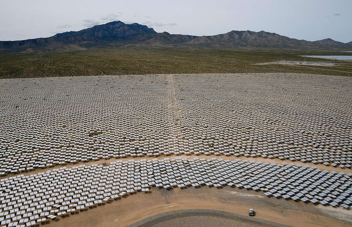 Heliostats at the Ivanpah Solar Electric Generating System are seen from above in front of the Clark Mountain Range on March 3, 2014 in the Mojave Desert in California near Primm, Nevada. The largest solar thermal power-tower system in the world, owned by NRG Energy, Google and BrightSource Energy, opened recently in the Ivanpah Dry Lake and uses 347,000 computer-controlled mirrors to focus sunlight onto boilers on top of three 459-foot towers, where water is heated to produce steam to power turbines providing power to more than 140,000 California homes. (Photo by Ethan Miller/Getty Images)