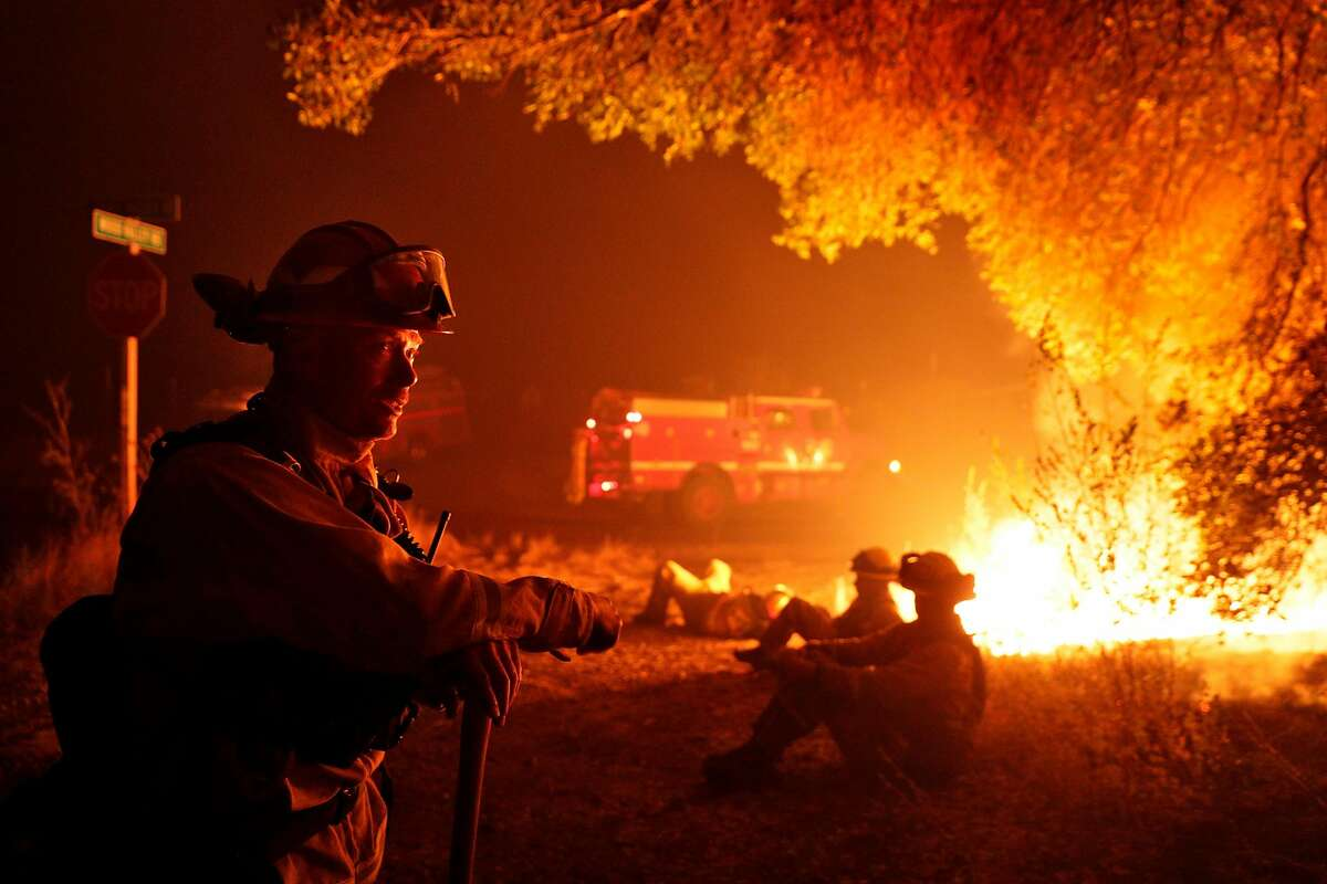 Firefighter Kevin Weaver from Station 1 in Petaluma keeps an eye on a flare up on Lovall Valley Road as crews continue to monitor several wildfires near Sonoma, Calif., on Friday, October 13, 2017. Emergency personnel were deployed to the perimeter of several fires as the threat of gusting winds had them worried that the fires would grow overnight.
