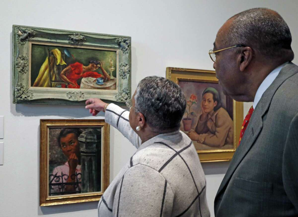 """Dr. Harmon and Harriet Kelley, who have been collecting African American art since the 1980s, talk about """"Night Letter,"""" a 1943 oil painting by Eldzier Cortor's that is in the original frame."""