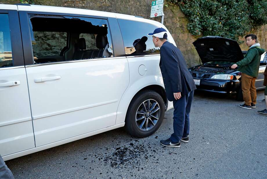 Chinese tourist AnQi Li looks into his rental van after it was broken into and a backpack was taken on Lombard Street. Photo: Scott Strazzante, The Chronicle