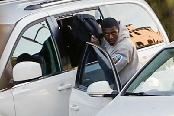 A man, later identified by police as Delon Barker, t akes a bag through a broken window of a van parked on Lombard St. on Tuesday, Jan. 30, 2018 in San Francisco, Calif.