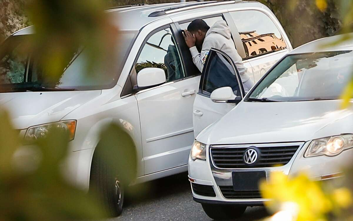 A man, later identified by police as Delon Barker,looks into a window of a van parked on Lombard St. on Tuesday, Jan. 30, 2018 in San Francisco, Calif.
