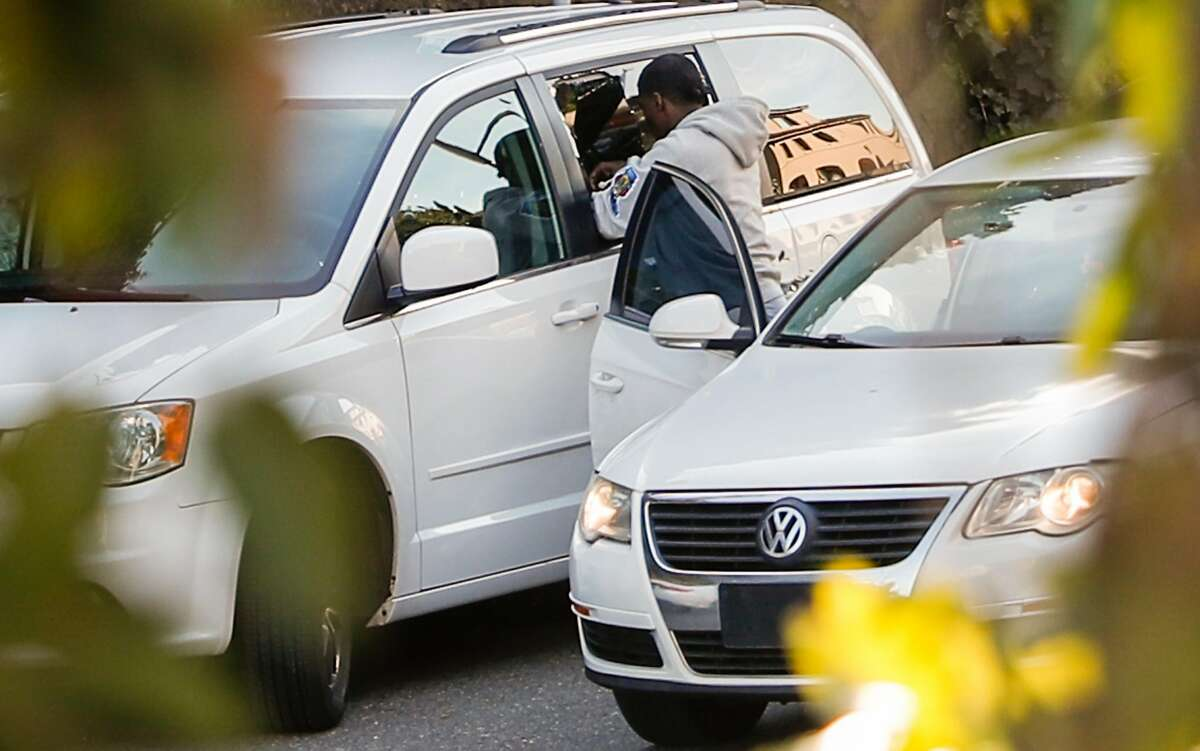 A man, later identified by police as Delon Barker,reaches into a broken window of a van parked on Lombard St. on Tuesday, Jan. 30, 2018 in San Francisco, Calif.